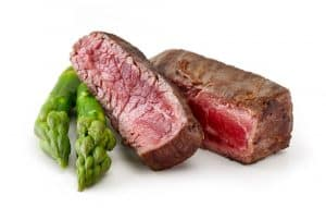 A close up of 2 slices of perfectly medium rare steak, cooked sous vide, with 2 spears of asparagus to the left